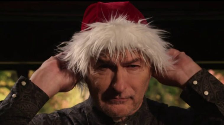 Joe Bob Briggs putting on a Santa hat