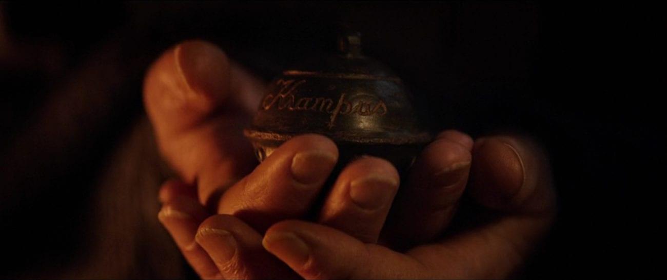 "Omi (Krista Stadler) holds a dark sleigh bell bearing the cursive inscription, ""Krampus,"" in the film, ""Krampus' (2015)."