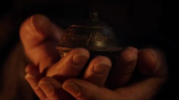 "Omi (Krista Stadler) holds a dark sleigh bell bearing the cursive inscription, ""Krampus,"" in the film, ""Krampus' (2015)."