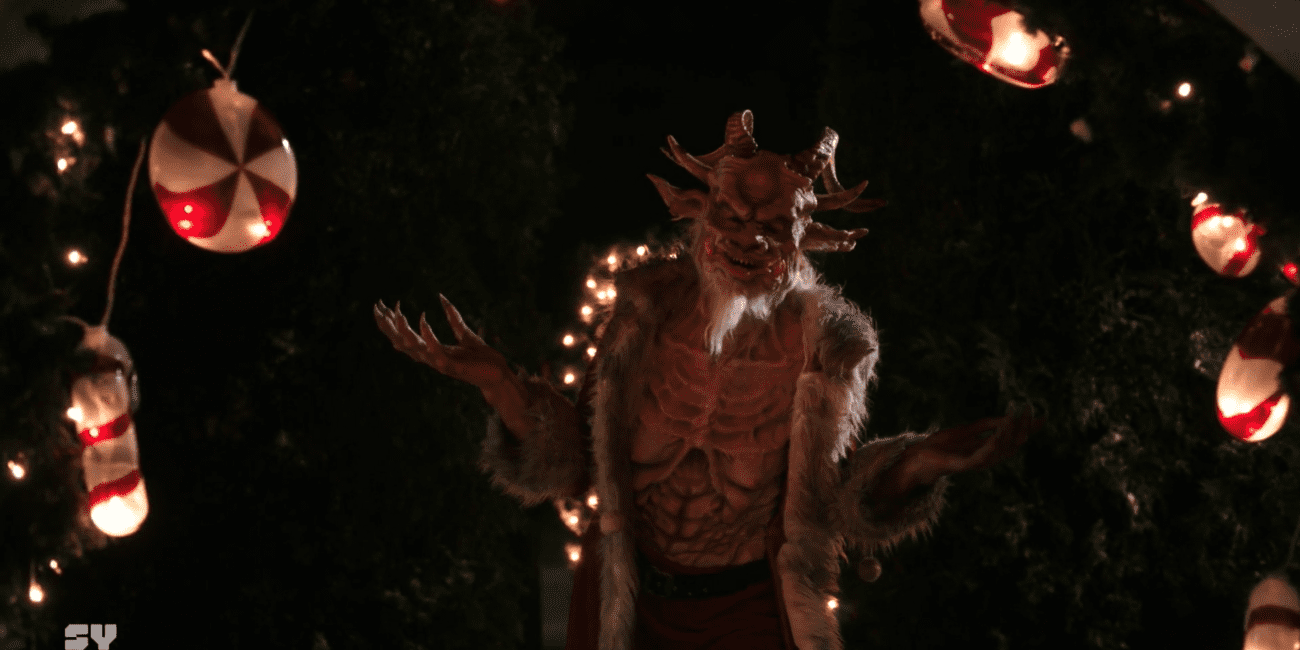 "Satan Claus (Jana Peck) shrugs with a smile, wearing a Santa coat, in the film, ""Letters to Satan Claus"" (2020)."