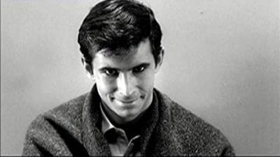 A young man looks into the camera with devious smirk.