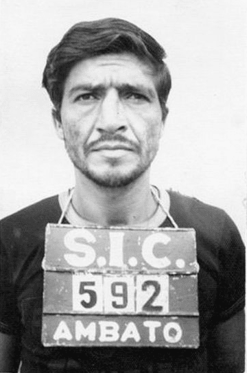 Pedro Lopez stands facing the camera at his arrest with his prison number drapped around his neck on a board