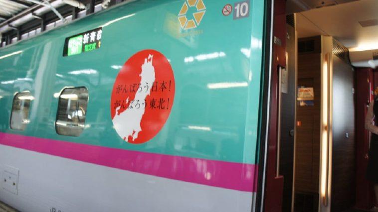 Tohoku Shinkansen Train in station with open door and attendant inside.