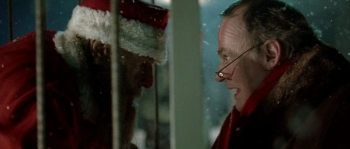 Brian Greene smiles as he comes face to face with a man dressed as Santa Claus who is being held in a cage