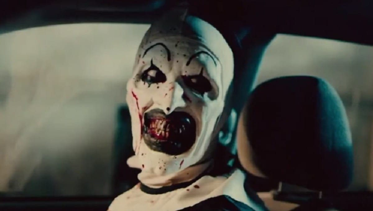 Art the Clown, a black-and-white mime-looking character with pointy features, grinning menacingly at someone from the passenger seat of a car. His makeup consists of a white base, large, overdrawn black lipstick, black eye makeup with two points extending from his bottom and top eyelids, raised pencil brows, and a small black dot on the tip of his long nose. Blood is splattered across his face and his teeth are brown and ragged.