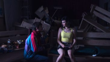 Remy, in a colorful jacket, and Danni, in a yellow tank top, talk in a church.