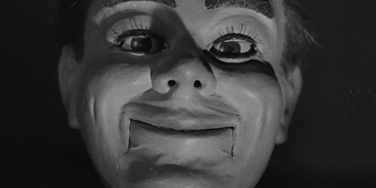 A close-up face of a dummy, staring into your soul with it's creepy smirk.