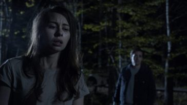 A night scene of a woman in the foreground and a man in the background in An Unquiet Grave