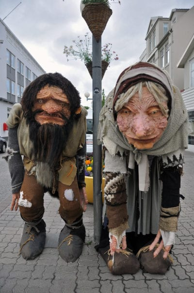 Costumes of giant witch and husband with tattered clothes and disproportionate limbs stand on city street