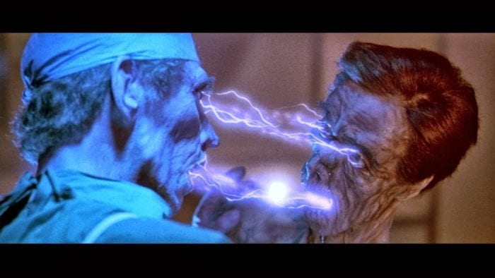 a man in surgical gear and a emaciated naked man have electricity flow from their eyes and mouth to one another