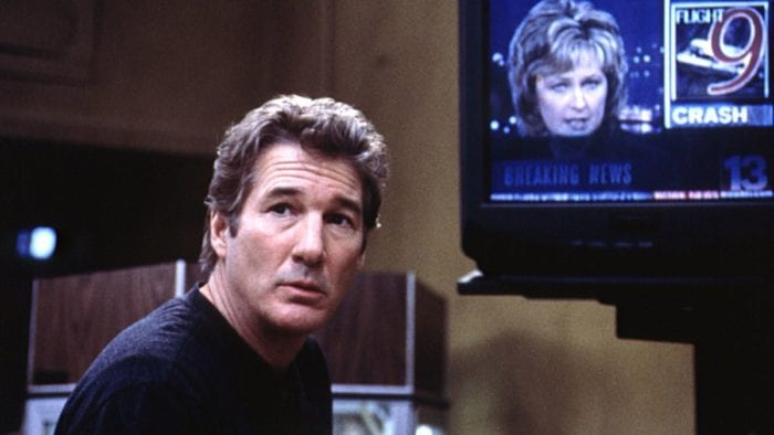 John (Richard Gere) looks off to the distance. A TV behind him is playing the news