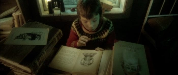 Pietri sits in his holiday sweater reading the ancient dark mythology of Santa claus as books are piled up around him