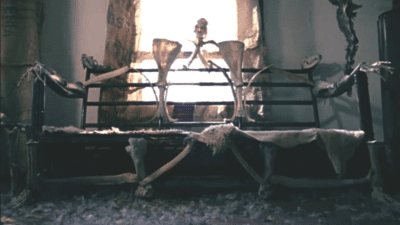 A couch made of human skeletal remains sits in front of a window A skull is clearly visible in the center and skeletal human hands rest on the arms.