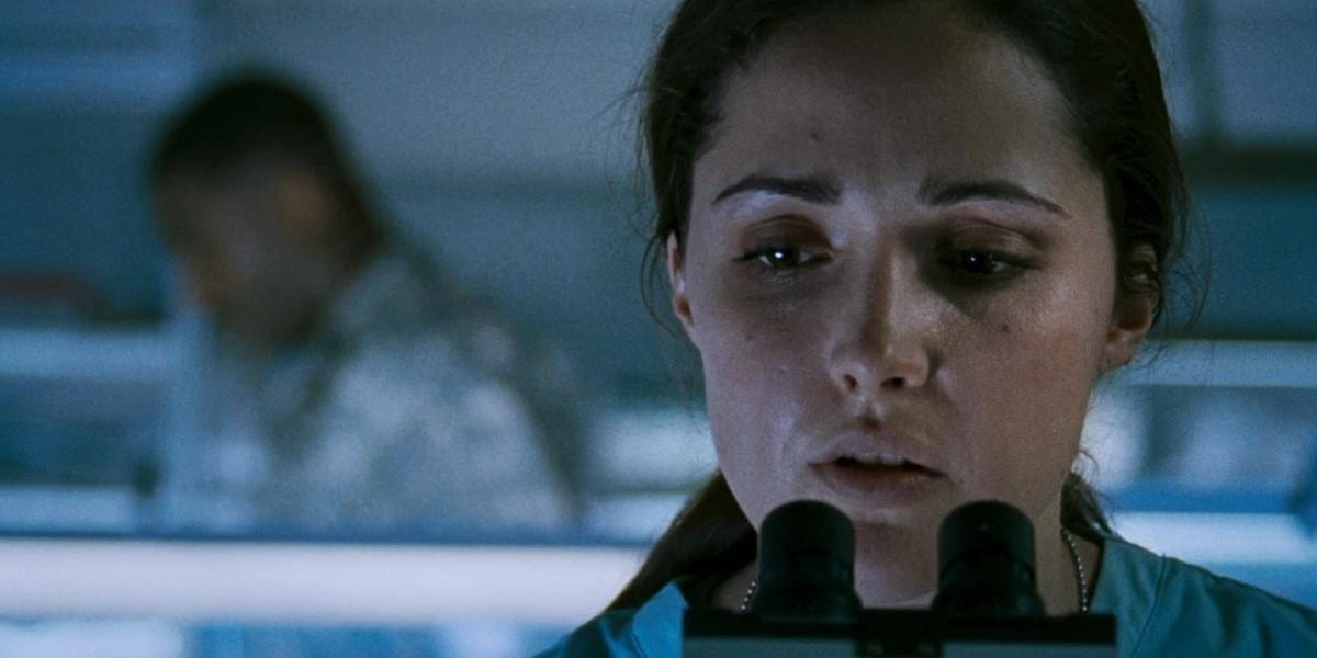 Scarlet Levy (Rose Bryne) looks at a microscope in a military lab.