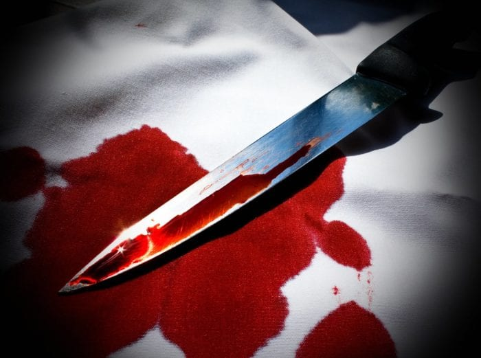 A carving knife lays on a table. it's blade coated in blood and that blood has soaked into a white table cloth.