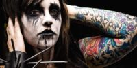 A picture of a woman with white and black face paint, a huge armband with nails sticking out of it, and tattoos up her arm stares out at you.