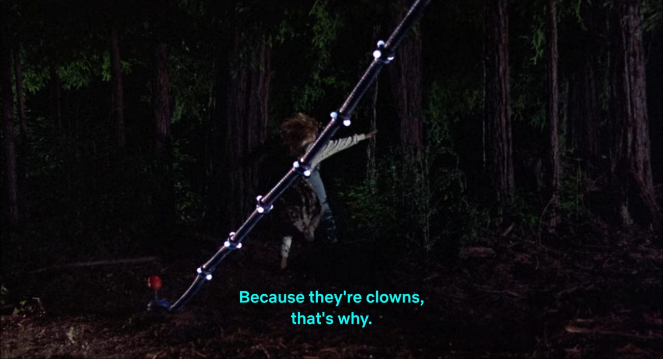 """Mike Tobacco yells, """"Because they're clowns, that's why,"""" as he and Debbie Stone (Suzanne Snyder) run away in the film, """"Killer Klowns from Outer Space"""" (1988)."""