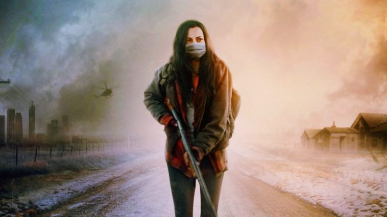 Ava Boone wears a mask and carries a gun while walking down a desolate road
