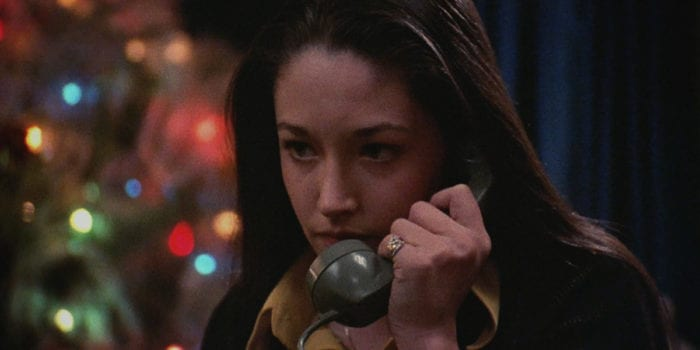 Jess is on the telephone in the foreground, Christmas tree lights can be seen in the background