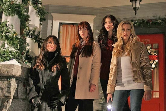 Leigh, Heather, Melissa, and Kelli stand on the doorstep of their sorority house, Christmas decorations on the door and pillars
