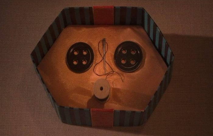 A hexagonal-shaped, stripey gift box containing two black buttons, a spool, and a needle and thread