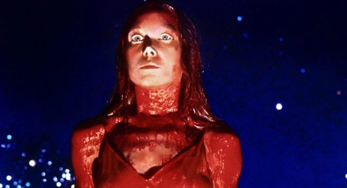 Sissy Spacek as Carrie stands covered in blood with a blue background