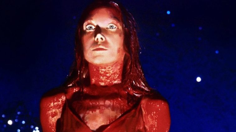 A young woman covered in blood stands straight with set mouth and wide eyes in Carrie.