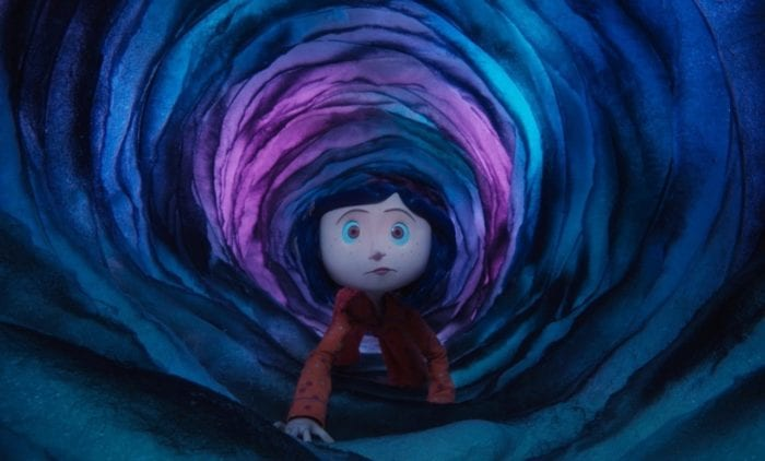 Coraline crawls through a blue and purple-lit tunnel