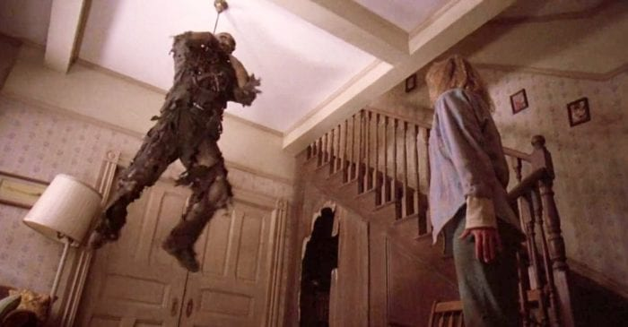 Jason hangs from the ceiling while Tina stands looking at him (Friday 13th Part 7)