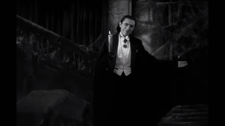 """Count Dracula (Béla Lugosi) holds one arm out in a beckoning welcome and holds a candle in the other hand in the film, """"Dracula"""" (1931)."""