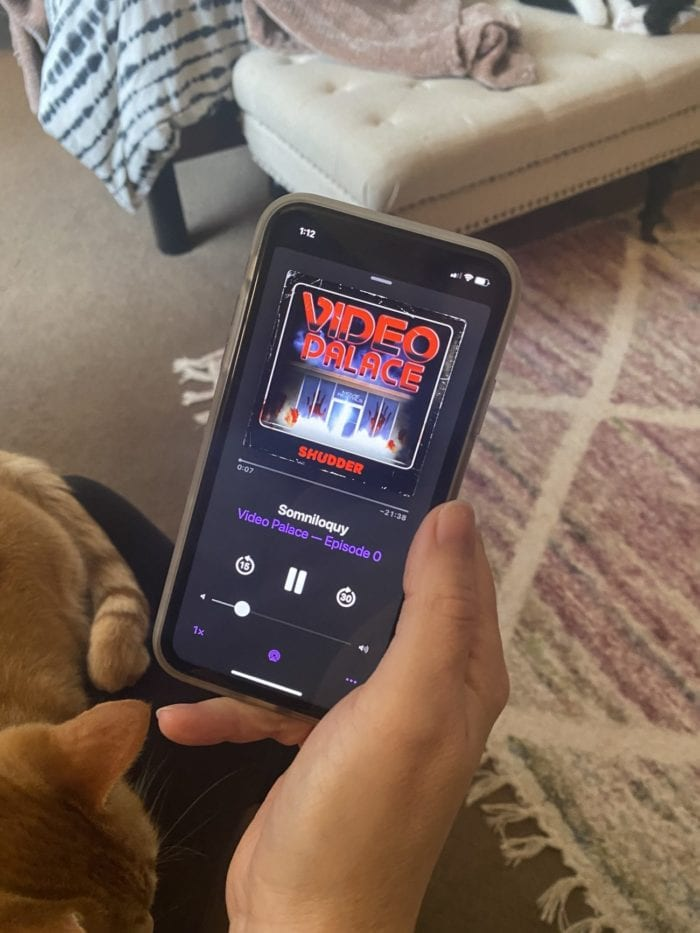 a phone with video palace playing on a podcast app held in a woman's hand, a cat sleeps in her lap and another cat sleeps on a bench in the background