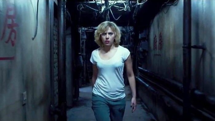 Lucy walks purposefully down a run-down corridor