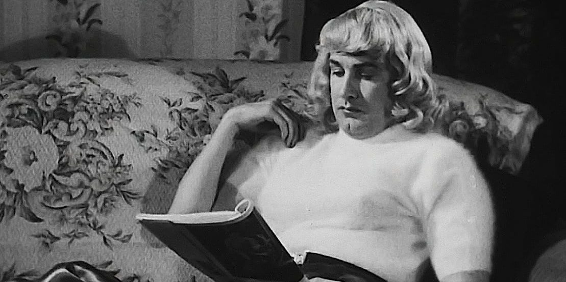 Ed Wood in the movie Glen Or Glenda, wearing an Angora sweater, blond wig, skirt and stockings as he sits on a couch.