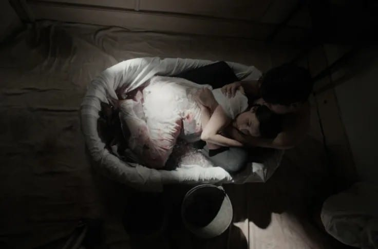 An overhead shot of a woman reclining in a bathtub of bloody water as man embraces her
