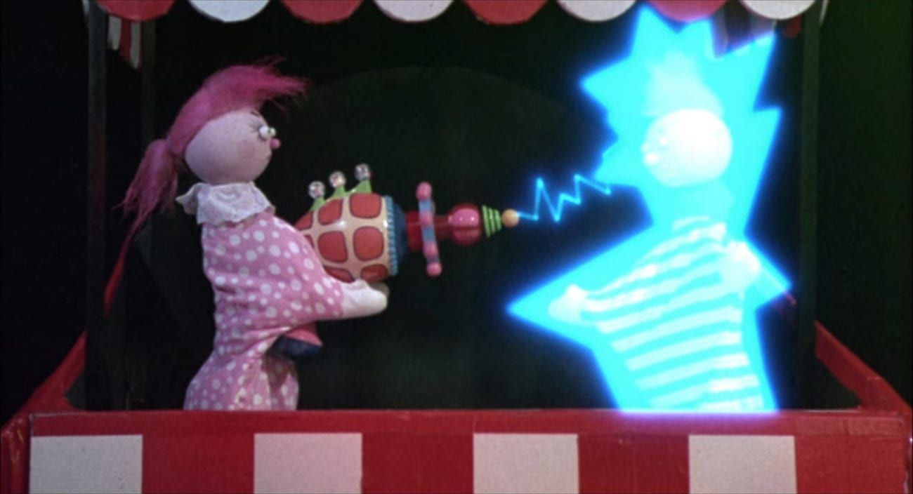 A female hand puppet shoots a colorfun ray gun at a male hand puppet, making him light up.