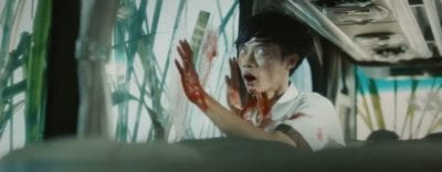A possessed orphan bashes his head against a bus window