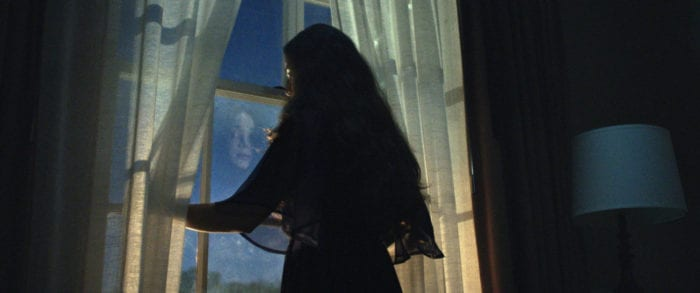 A silhouette of a woman looking out a window into the night, parting the white curtains