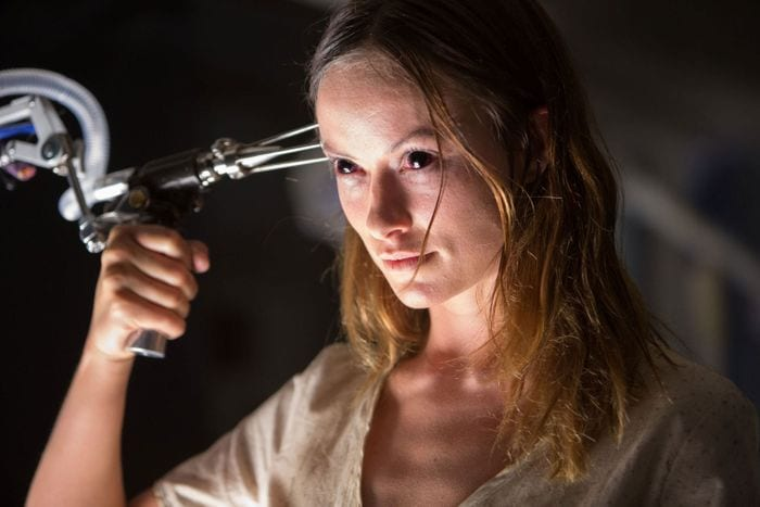 Zoe from The Lazarus Effect holds a 3-needle gun to her head, her eyes black