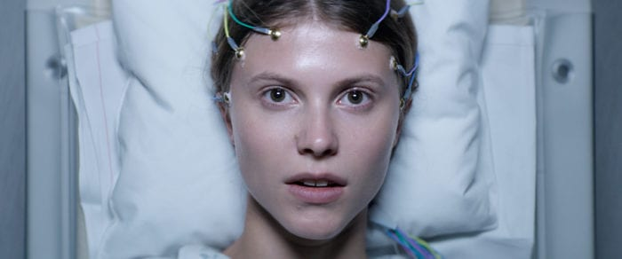 Thelma is lying on a hospital bed, wires attached to her forehead