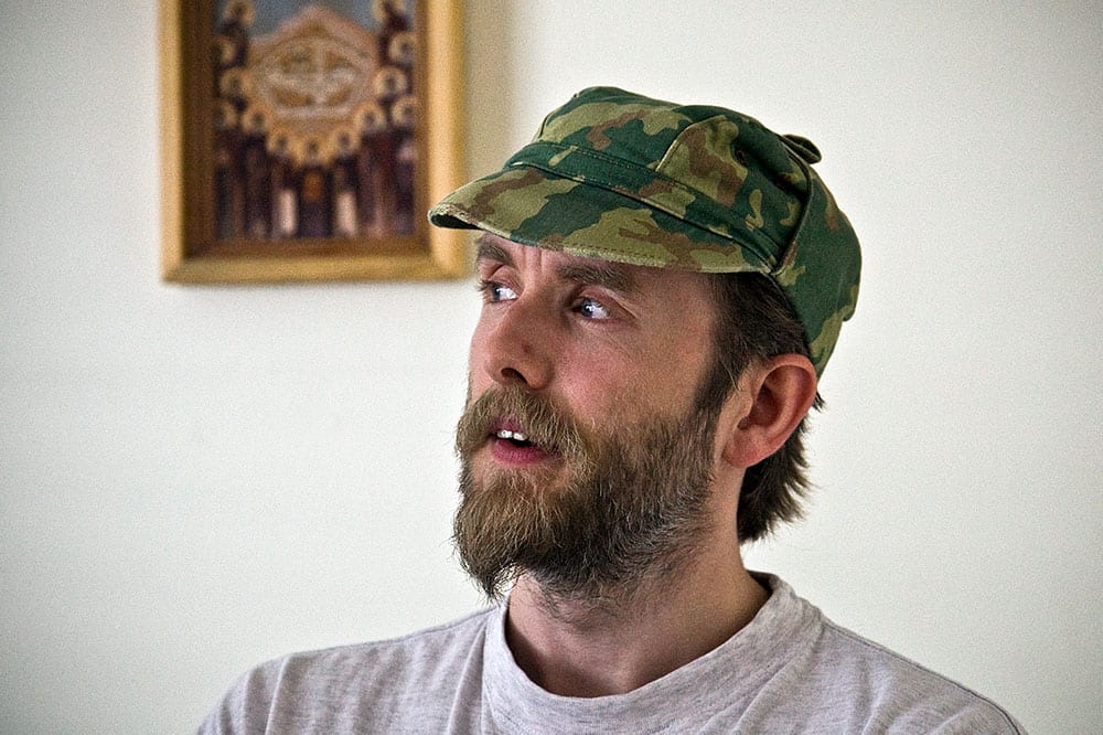 Varg Vikernes is being interviewed from pirson. His face has a goatee beard, he's wearing a white t-shirt and a camo baseball cap and is looking away from the camera as if he is thinking.