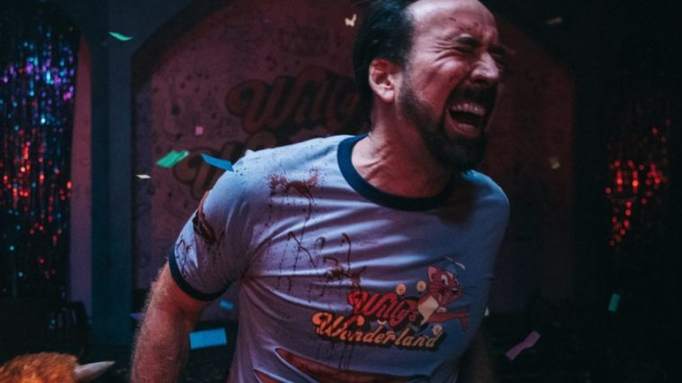 Nicolas Cage's face contains a pained look as he winces toward the camera with a bloodied and ripped Willy's Wonderland shirt on