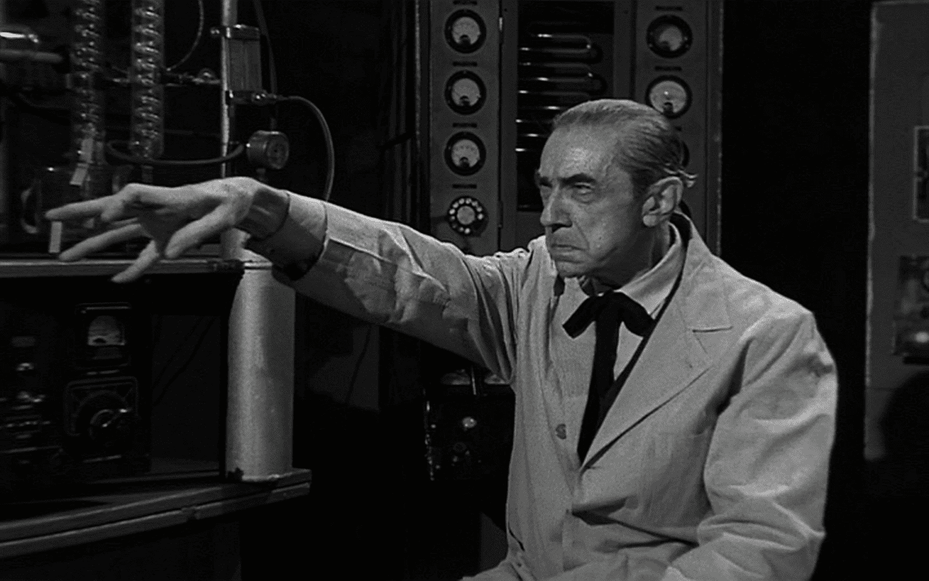 Bela Lugosi In Bride Of The Monster. Dressed in mad scientist clothes, Lugosi sits, arm streteched out before him in a claw.