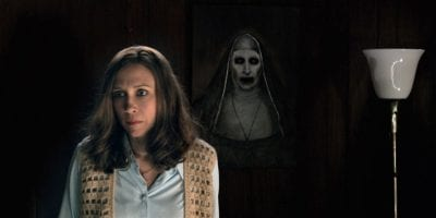 Vera Farming as Lorraine Warren looks frightened while a ghostly, demonic nun stands behind her in the dark.