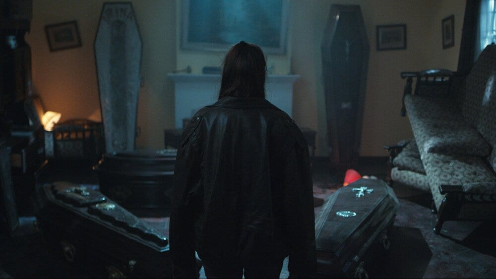 A girl looking at coffins inside her house