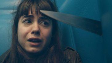 A girl looking at a knife stabbing through a wall
