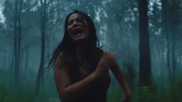 A woman runs screaming through the woods