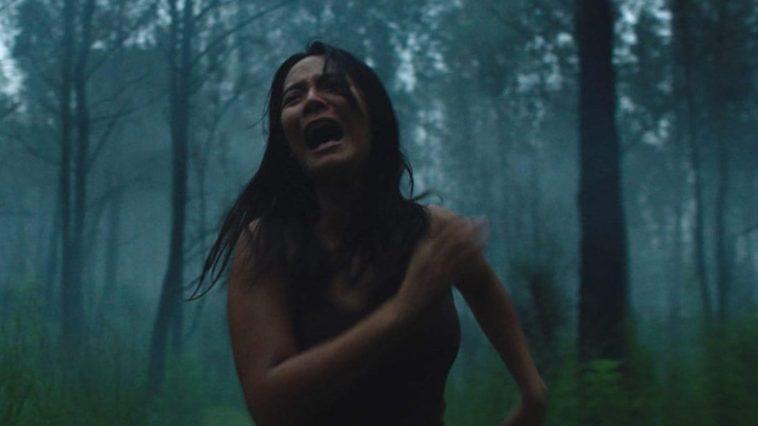 A woman runs screaming through the woods