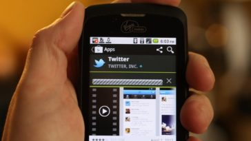 A hand holds a mobile phone with the Twitter app displayed on the screen.