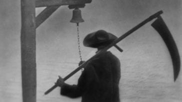 A man rings a bell while wielding a scythe.
