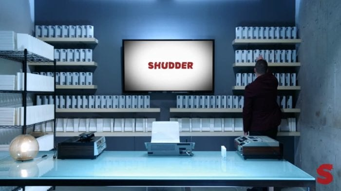 a film production lab with rows of blank white tapes lined up surrounding a large tv screen with the word shudder written on it, a large man in a black suit grabs a tape off a shelf to the right